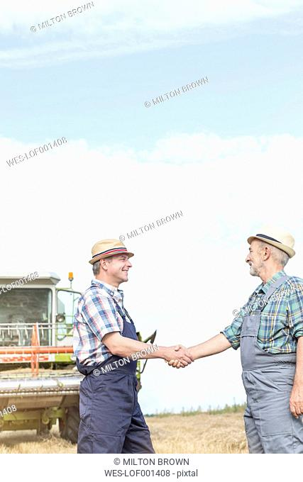 Two farmers on field shaking hands