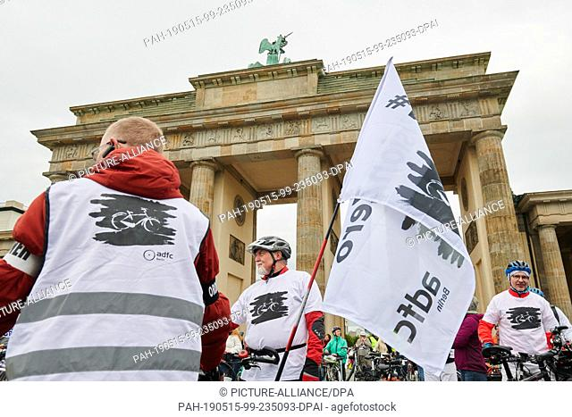 15 May 2019, Berlin: Participants of the Ride of Silence stand with their bikes and flags in front of the Brandenburg Gate