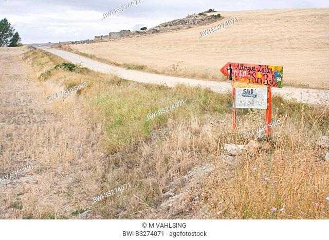 direction sign at the Way of St. James through dried up meadow and field landscape showing the way to the pilgrim's hostel in San Bol, Spain, Kastilien und Len