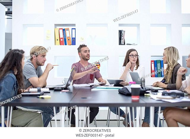 Creative office people having a meeting around a boardroom table