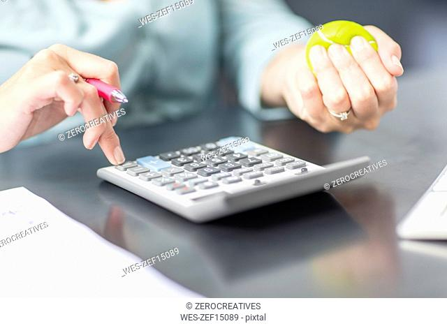 Woman at desk in office using calculator and stress ball