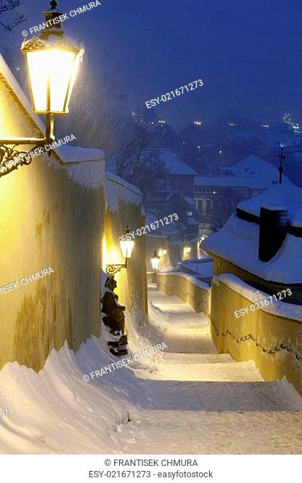 narrow stairway from hradcany castle with gas lanterns during heavy snowfall