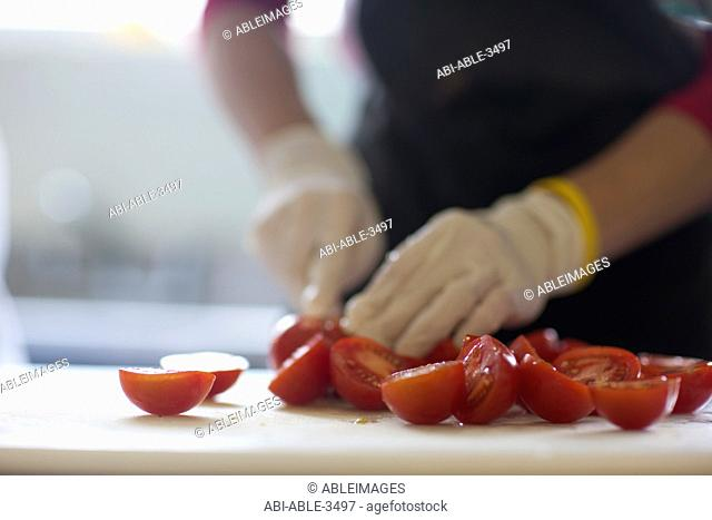 Close up of a worker hands cutting fresh tomatoes
