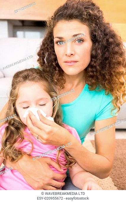 Worried mother helping her little daughter blow her nose