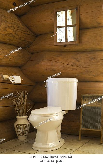 Toilet in corner of main bathroom inside a cottage style log home, Quebec, Canada