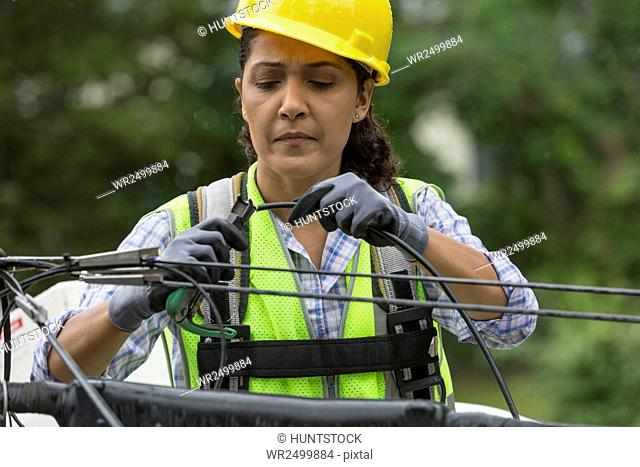 Hispanic female cable lineman crimping the cables in bucket lift
