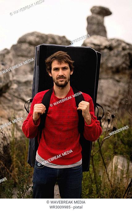 Confident man standing with mattress