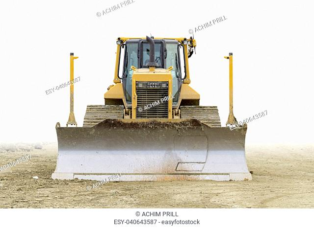 frontal shot of ayellow bulldozer at a loamy construction site,partly isolated in white back