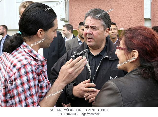 Federal Minister of Economy Sigmar Gabriel (SPD, C) speaking with residents of a refugee centre during a visit there in Wolgast, Germany, 31 July 2015