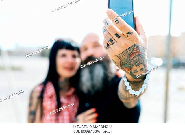 Mature tattooed hipster couple taking selfie, close up of hand