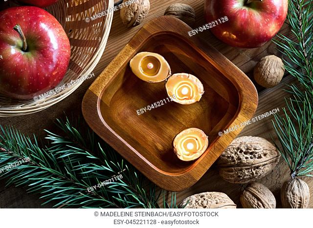 Christmas decoration - apples, pine branches, walnuts and floating candles made from nutshells in a bowl of water, top view