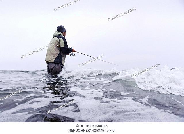 Man fishing on coastline