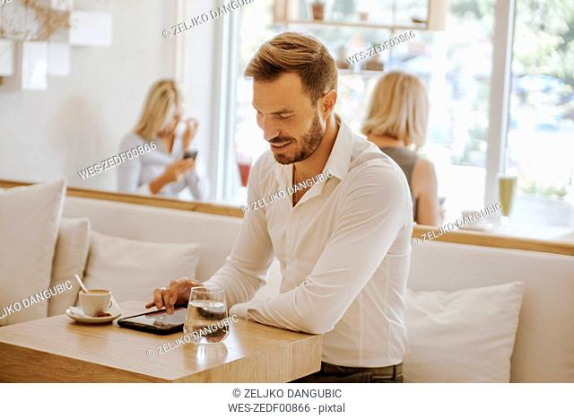 Man using tablet in a cafe with two women in background