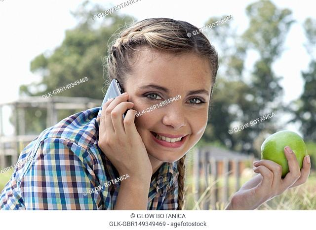 Woman talking on a mobile phone while eating apple