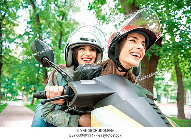 Carefree lesbian couple is driving by scooter on speed. Woman is sitting and embracing her friend with joy. They are looking forward with aspiration and smiling