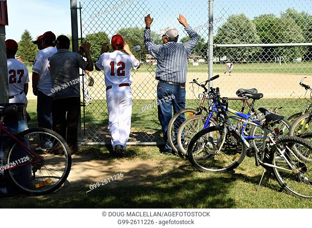 Players and fans watch game baseball game action in Leamington, Ontario, Canada