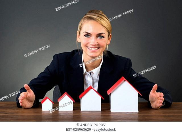 Portrait of happy businesswoman with model houses arranged in graph order