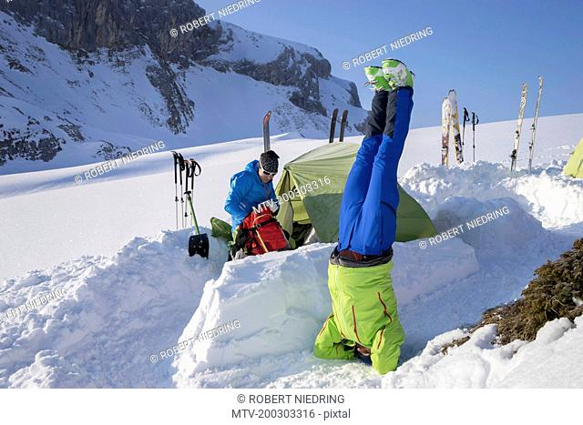 Man doing headstand pose of yoga at camp on snowcapped mountain, Tyrol, Austria