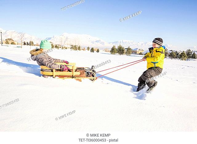 Children (8-9) playing with sled in snow