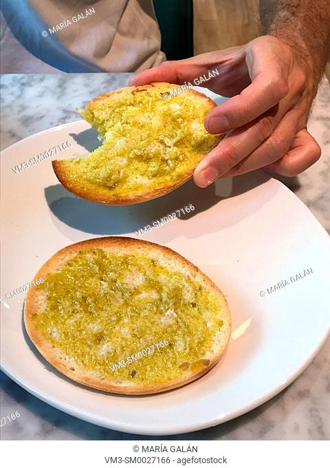 Man eating bread with olive oil. Spain