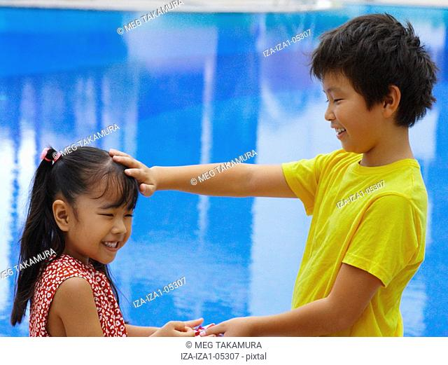 Close-up of a girl giving a gift to a boy at the poolside