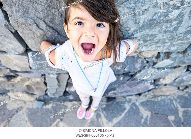 Portrait of little girl with mouth open in front of a rock face