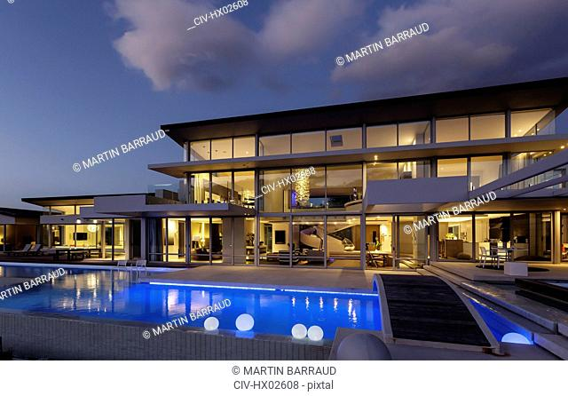 Illuminated modern luxury home showcase exterior with swimming pool at night