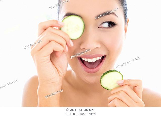 MODEL RELEASED. Young Asian woman holding cucumber in front of eye, portrait