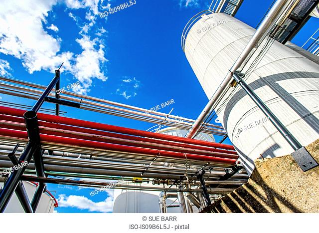 Low angle view of industrial piping and storage tanks at biofuel plant