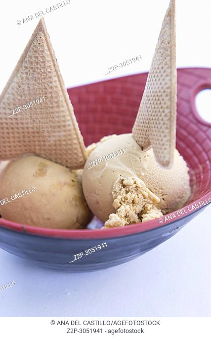 Almond or turron ice cream scoops with cookies for dessert Spain