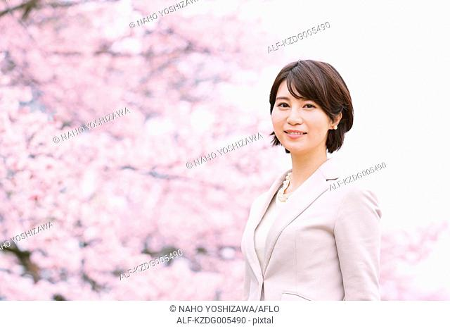 Japanese woman with cherry blossoms in a city park