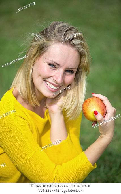 Pretty blonde woman with apple in park