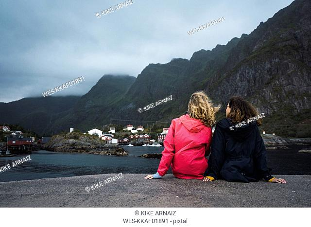 Norway, Lofoten, rear view of two young women sitting on a pier at the coast