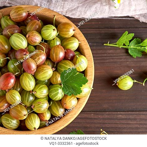 round wooden bowl with green and yellow gooseberries, brown table, top view
