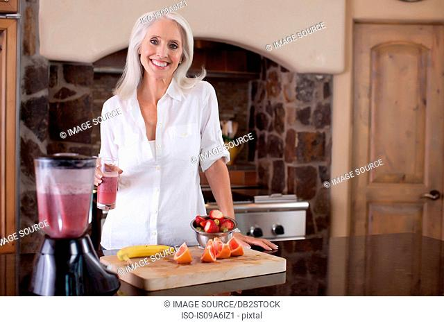Older woman making smoothie in kitchen