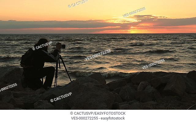 Photographer taking photos of seascape at sunset