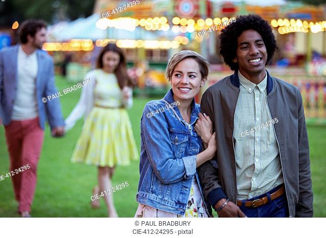 Young multiracial couple smiling while walking in amusement park