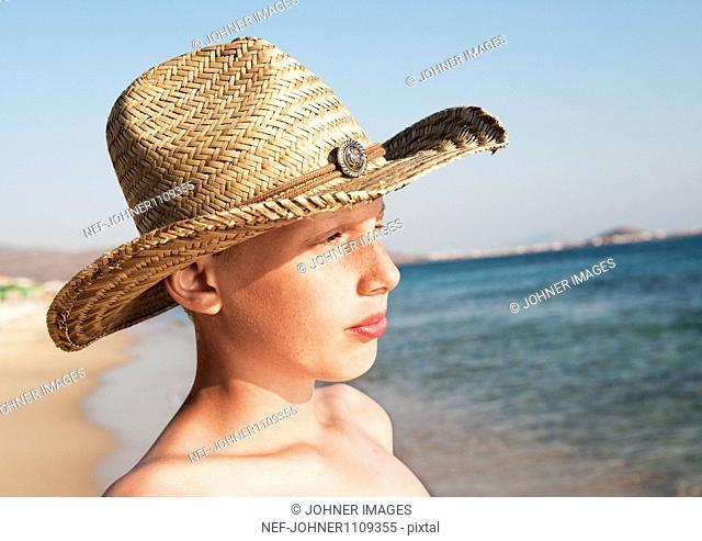 Portrait of teenage boy wearing straw hat on beach