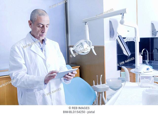 Hispanic dentist using digital tablet in office