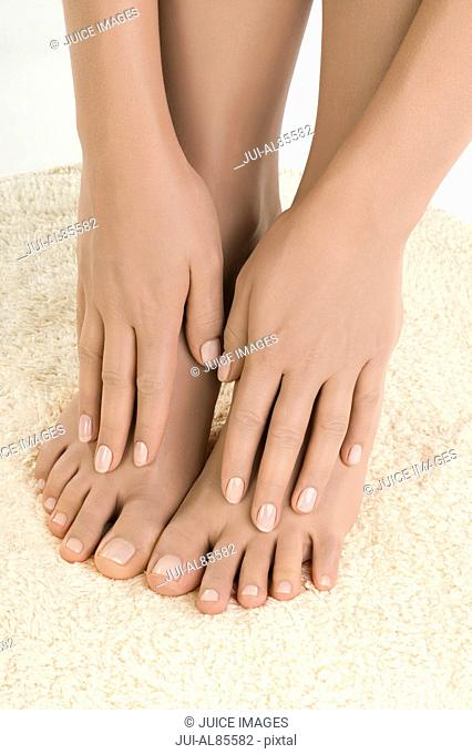 Close up of woman's hands caressing bare feet on rug