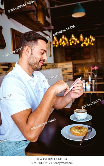 Young man having cup of coffee and pastry
