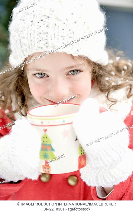 Girl wearing winter clothing drinking from a cup with a Christmas motif