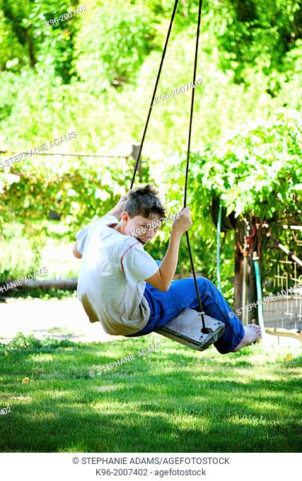 Young boy making faces while swinging
