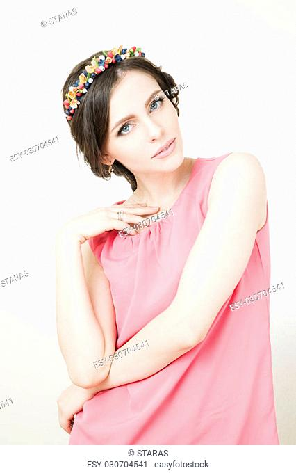 Studio portrait of a young beautiful woman with flower wreath on head. Make-up and hairstyle with flowers