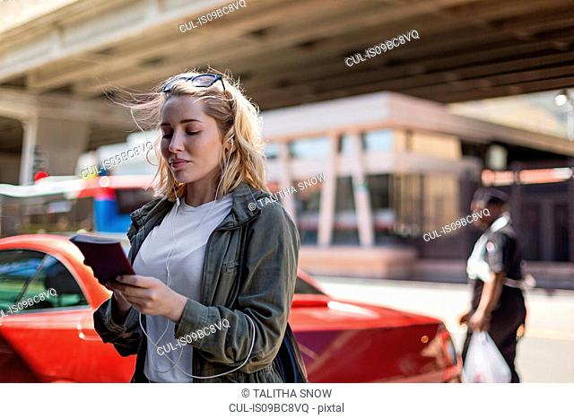 Woman using mobile phone on street, Cape Town, South Africa