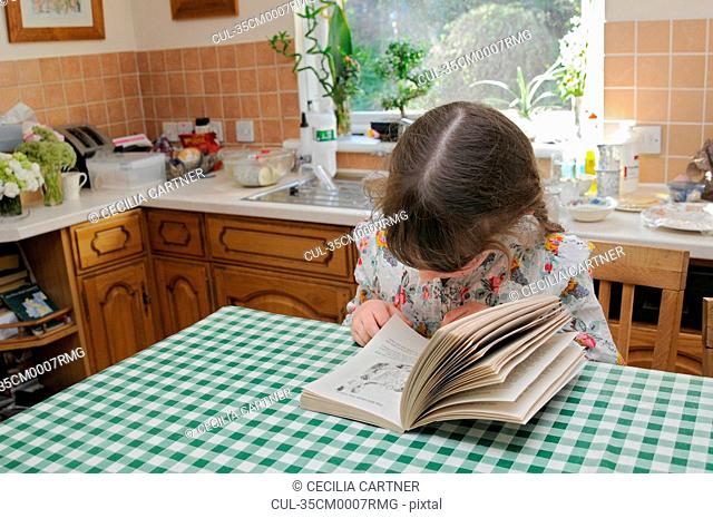 Girl reading at kitchen table
