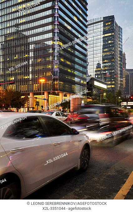 Street traffic in Futian Central Business District at dusk. Shenzhen, Guangdong Province, China