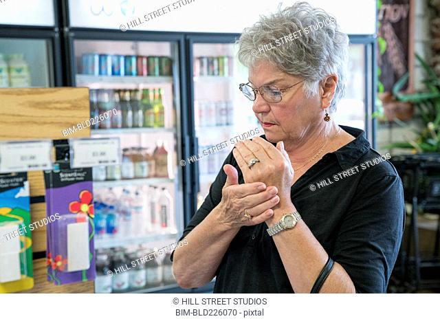 Caucasian woman sampling lotion in nutrition store