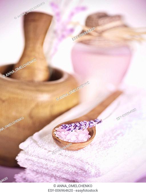 Image of spa accessories, white soft towel, wooden mortar, herbal oil, spoon with sea salt and lavender flower on massage table, toiletries, natural cosmetics