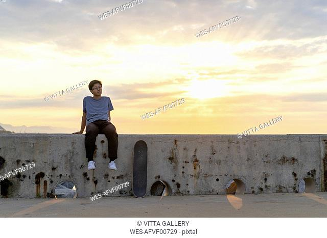 Young Chinese man sitting on wall at sunrise